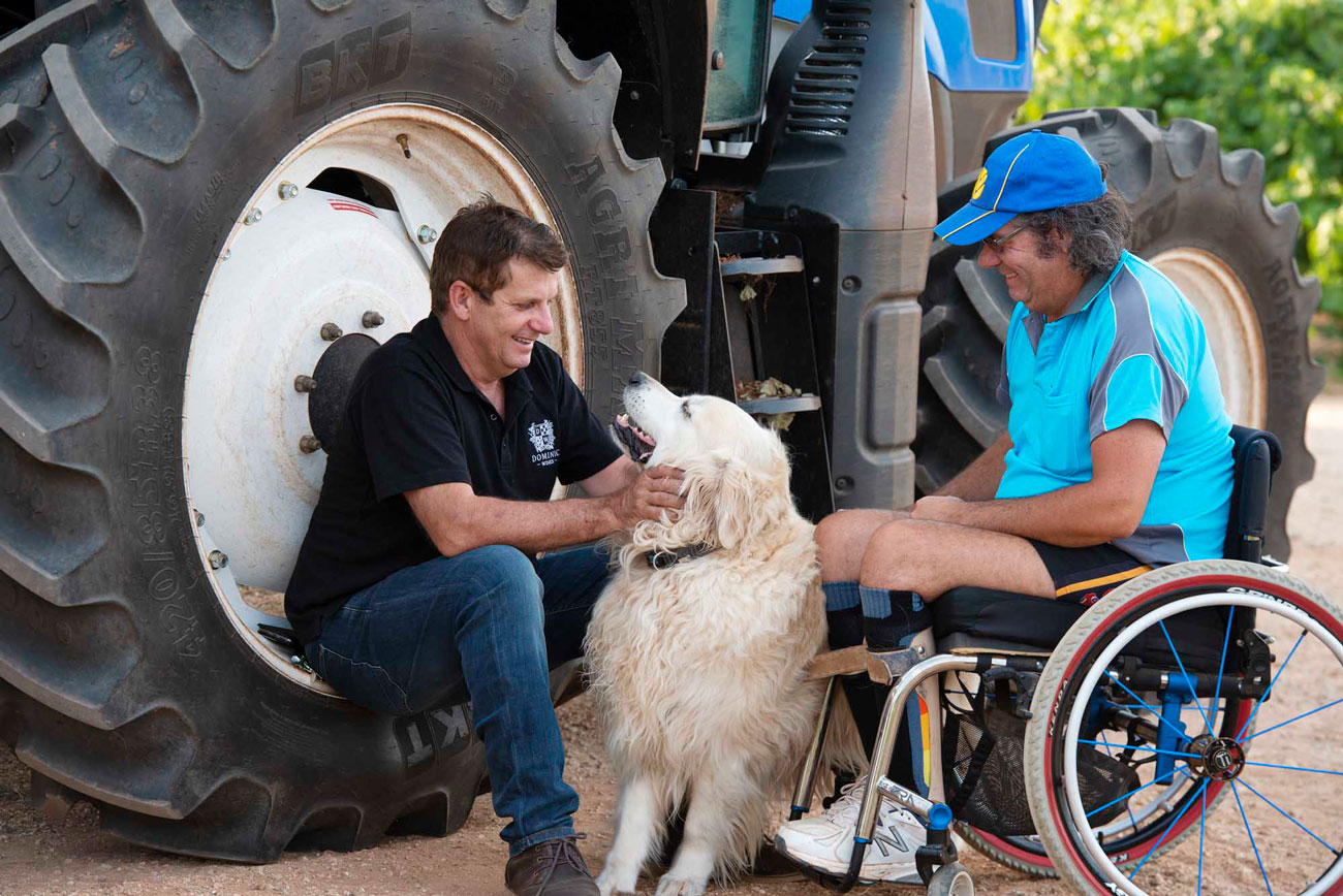 Brian sitting with Charlie and dog next to tractor wheel