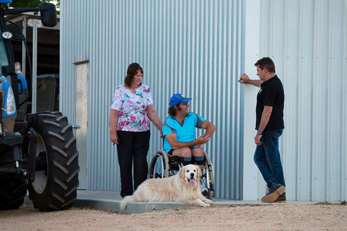 Charlie, his wife and dog talking to Brian next to a shed and tractor