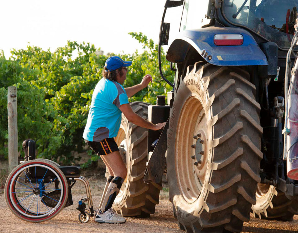 Charlie standing up out of his wheelchair getting into a tractor