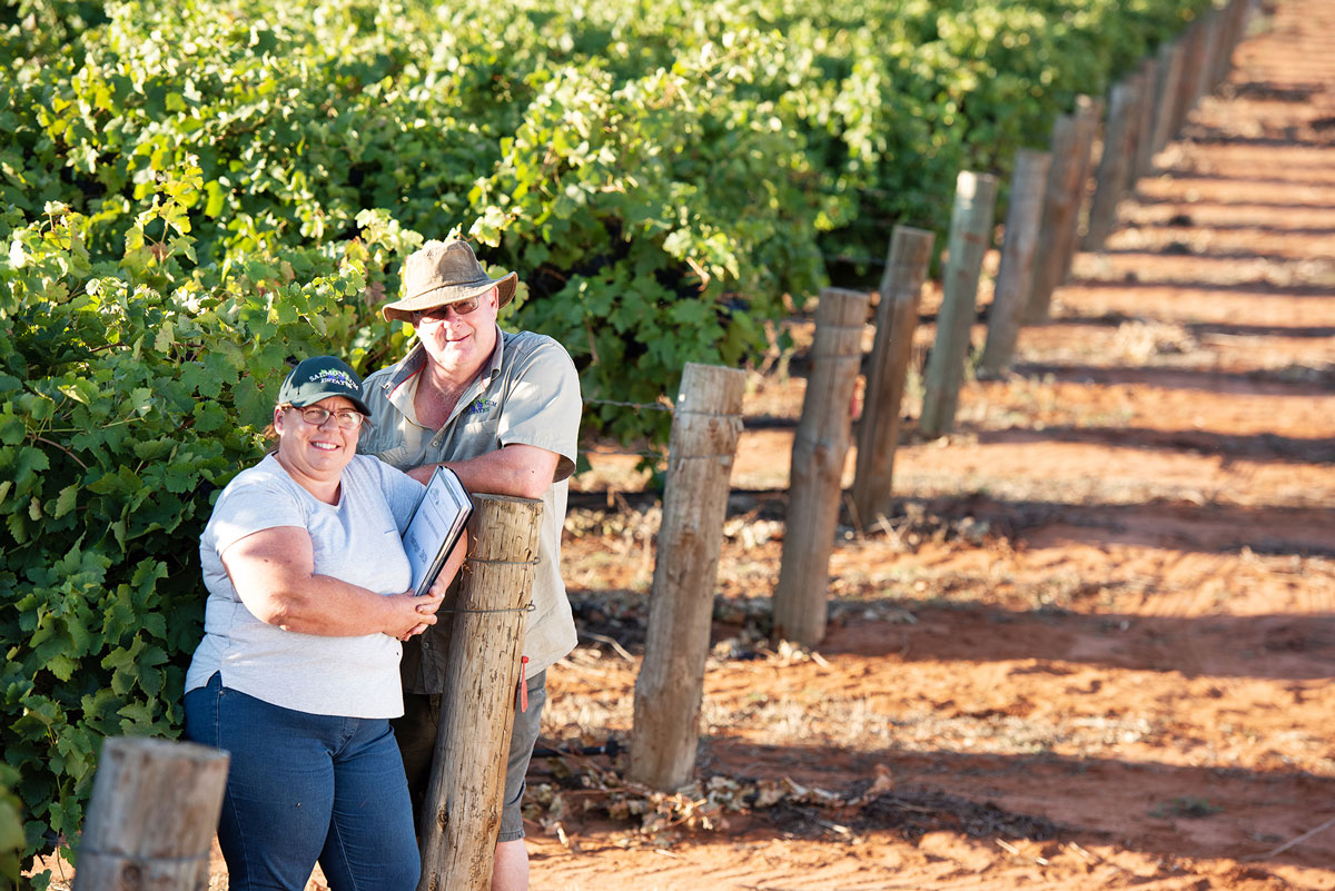 man and woman standing next to riverland vines